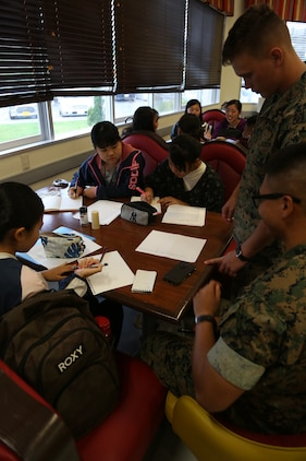 CAMP COURTNEY, OKINAWA, Japan – Students from the local community work on homework with Marines during Camp Courtney's Summer English class Aug. 16 at the Camp Courtney Mess Hall, Okinawa, Japan.