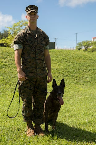 CAMP HANSEN, OKINAWA, Japan – Cpl. David Adams and military working dog Shadow pose for a photo Aug. 31 at the kennels on Camp Hansen, Okinawa, Japan.