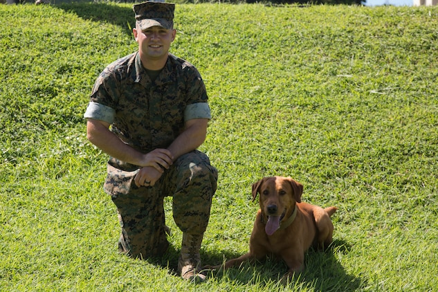 CAMP HANSEN, OKINAWA, Japan – Cpl. Alex Marquissee and military working dog Gage pose for a photo Aug. 31 at the kennels on Camp Hansen, Okinawa, Japan.