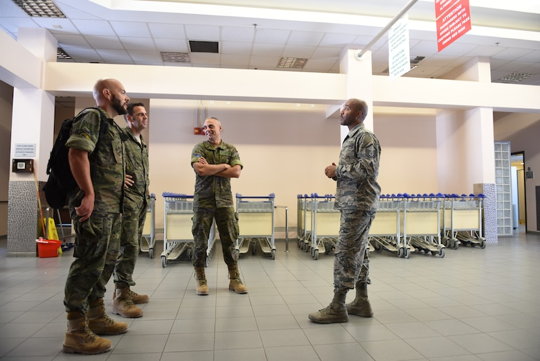 (Right) U.S. Air Force Master Sgt. Robert Thurman, air terminal operation center& passenger Services section chief, 728th Air Mobility Squadron, shows members of the Spanish Army around the passenger terminal at Incirlik Air Base, Turkey, Sept. 7, 2018.