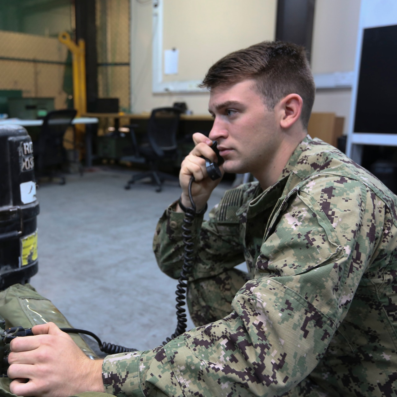 A sailor uses a radio.