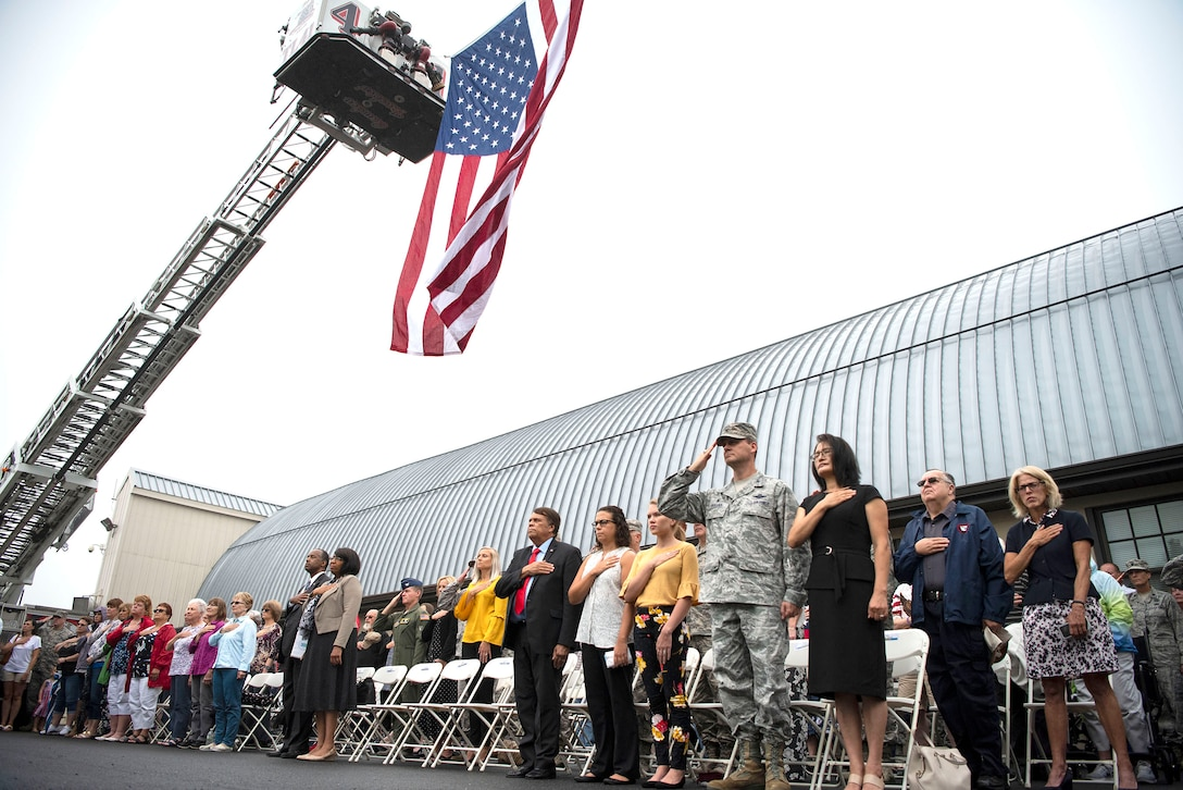 Attendees stand during the National Anthem at a 9/11 Memorial Service Sept. 11, 2018, at the Air Mobility Command Museum on Dover Air Force Base, Delaware. The large flag overhead was suspended from the ladders of firetrucks from Camden-Wyoming and Dover fire companies.