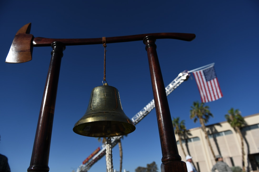 A 99th Civil Engineer Squadron ceremonial bell is on display during a 9/11 remembrance ceremony held at the U.S. Air Force Warfare Center flag pole, Nellis Air Force Base, Nevada., Sept. 11, 2018.  Nellis Airmen remember 9/11 with a flag lowering, moment of silence and ringing a ceremonial bell. (U.S. Air Force photo by Lorenz Crespo)