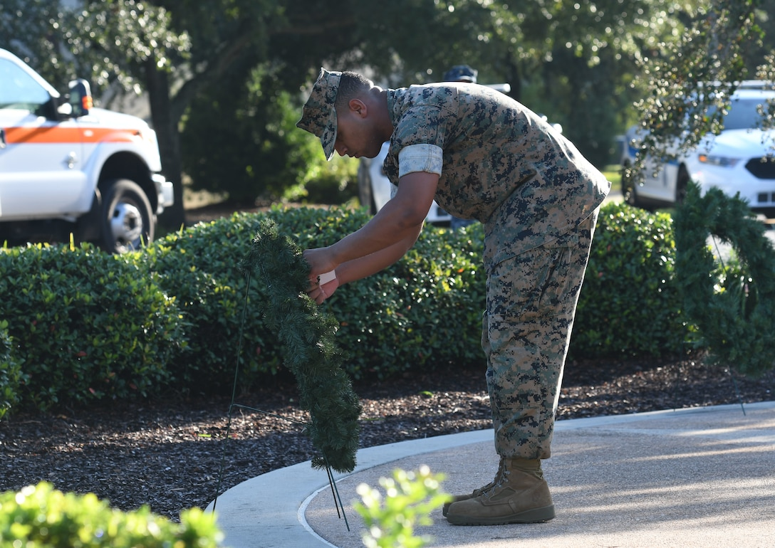 U.S. Marine Corps Private 1st Class Victor Vargas, Keesler Marine Detachment student, places a name tag on a memorial wreath during a 9/11 ceremony in front of the 81st Training Wing headquarters building at Keesler Air Force Base, Mississippi, Sept. 11, 2018. The event honored those who lost their lives during the 9/11 attacks. (U.S. Air Force photo by Kemberly Groue)