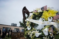 A wreath of yellow flowers stands in front of the Joint Base McGuire-Dix-Lakehurst 9/11 Memorial following a commemorative ceremony at the Timmermann Center on JB MDL, N.J., Sept. 11, 2018. The memorial site contains twisted steel beams that were salvaged from ground zero, and was officially completed in 2016.
