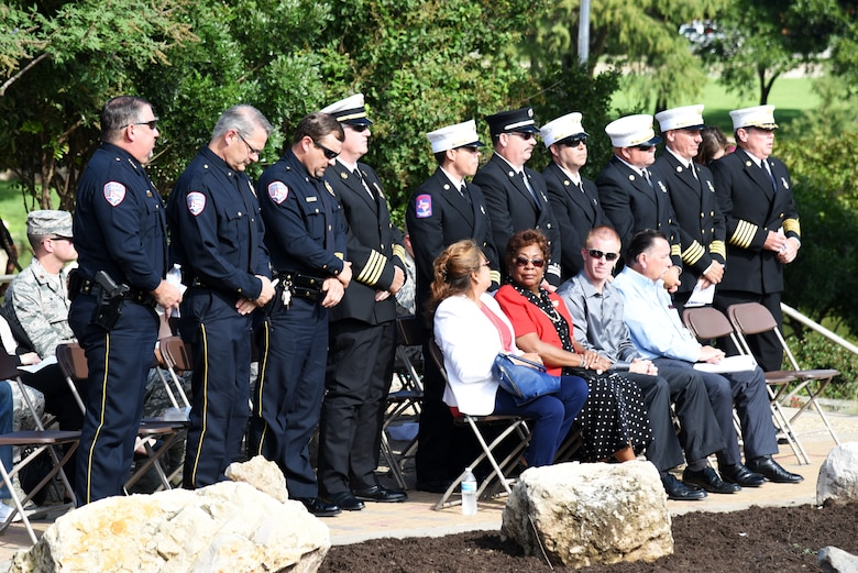 Police officers and firefighters stand to be recognized during the 9/11 remembrance ceremony at the 9/11 memorial near the San Angelo Museum of Fine Arts in San Angelo, Texas, Sept. 11, 2018. U.S. Air Force Col. Ricky Mills, 17th Training Wing commander, asked them to stand to be recognized because, like 403 first responders that died on Sept. 11, 2001, they are willing to put their lives on the line for others. (U.S. Air Force photo by Staff Sgt. Joshua Edwards/Released)