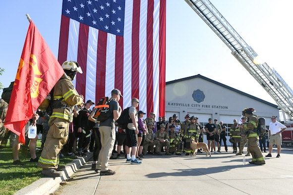 Staff Sgt. Caleb Saunders (far right), from the 775th Civil Engineering Squadron Fire Department, reads about one of the 9/11 fallen at the Kaysville Fire Station during one of the stops of the 9/11 Memorial Ruck March.