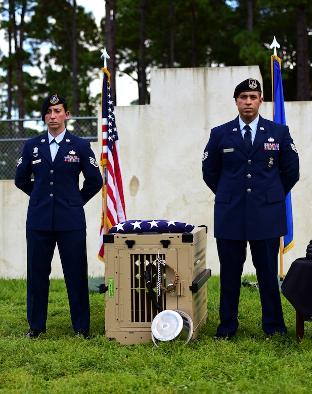 U.S. Air Force Staff Sgt. Caitlin Bourque, left, and Staff Sgt. Marcus Lavalais, right, 325th Security Forces Squadron military working dog (MWD) handlers, stand alongside the effects of MWD Jack during Jack's memorial service at Tyndall Air Force Base, Fla., Sept. 7, 2018. Jack was an explosives and patrol dog who shared a special bond with his handlers. MWDs enhance security forces capabilities to protect resources, enforce military laws, suppress drugs, detect explosives and protect installations. (U.S. Air Force photo by Senior Airman Isaiah J. Soliz)