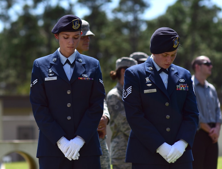 U.S. Air Force Airman 1st Class Arleen Michael, left, and Staff Sgt. Katelyn Grau, right, 325th Security Forces Squadron Airmen, show reverence during a military working dog (MWD) memorial service at Tyndall Air Force Base, Fla., Sept. 7, 2018. Jack, a Belgian Malinois, was an explosives and patrol dog who shared a special bond with his handlers. MWDs are afforded military customs and courtesies. (U.S. Air Force photo by Senior Airman Isaiah J. Soliz)