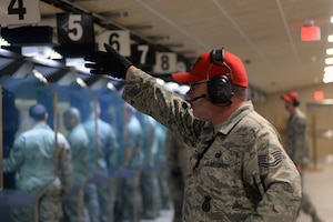Tech. Sgt. Brian Stuart, 55th Security Forces Squadron (SFS) combat arms NCO in charge, gives the all clear signal after a round of shots are fired during an Excellence in Competition (EIC) pistol contest Aug. 30, 2018, at Offutt Air Force Base, Nebraska. This is the second EIC event the 55th SFS has had since completing the renovations of their combat arms shooting range earlier this year. The first focused on the use of rifles. (U.S. Air Force photo by Kendra Williams)
