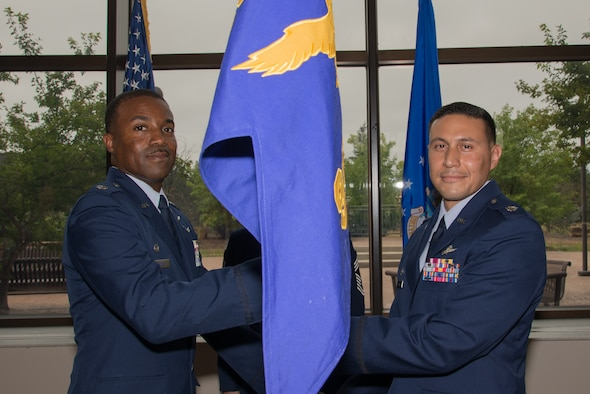 Lt. Col. Silas Darden, left, the 960th Cyberspace Operations Group Detachment 2 commander, passes the 960th NOS guidon to Lt. Col. Fernando Ruiz as he takes command of the squadron during a change of command ceremony at Peterson Air Force Base, Colorado, Sept. 8, 2018.