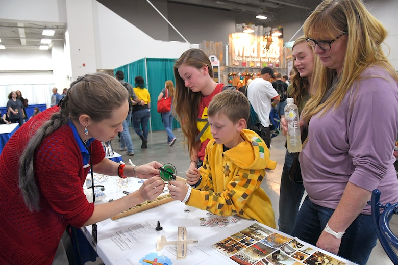 FanX visitors try out toys designed to demonstrate scientific principles and talk with Rachael Beal, 309 Software Maintenance Wing, volunteer at the HAFB STEM Outreach booth, Sept. 7, Salt Lake City.