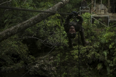 A Marine with Echo Company, Battalion Landing Team, 2nd Battalion, 5th Marines, climbs across a cable during an endurance course at Jungle Warfare Training Center, Camp Gonsalves, Okinawa, Japan, July 30, 2018.