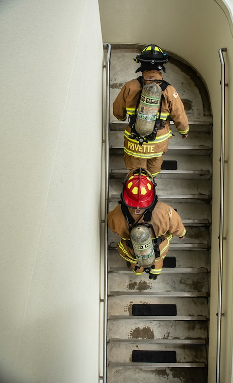 U.S. Air Force Senior Airman Forrest Privette, top, 18th Civil Engineer Squadron driver operator, and Staff Sgt. Nicholas Schafer, 18th CES lead firefighter, walk up a flight of stairs during the Kadena Fire Emergency Services 9/11 Memorial Stair Climb Sept. 11, 2018, at Kadena Air Base, Japan. Firefighters participating in the event donned approximately 60 pounds of gear and climbed a total of 110 flights of stairs to simulate the climb firefighters made during the Sept. 11, 2001, terrorist attacks at the World Trade Center in N.Y.  (U.S. Air Force photo by Staff Sgt. Micaiah Anthony)