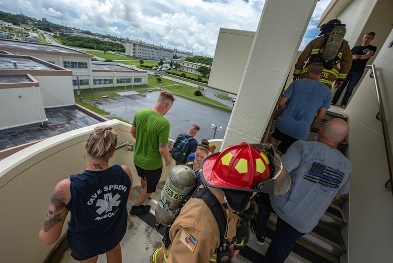 Participants of the Kadena Fire Emergency Services 9/11 Memorial Stair Climb walk up and down a flight of stairs Sept. 11, 2018, at Kadena Air Base, Japan. The event was open to all personnel with base access to honor the sacrifice first responders made during the Sept. 11, 2001, terrorist attacks and remember the victims of that day. (U.S. Air Force photo by Staff Sgt. Micaiah Anthony)