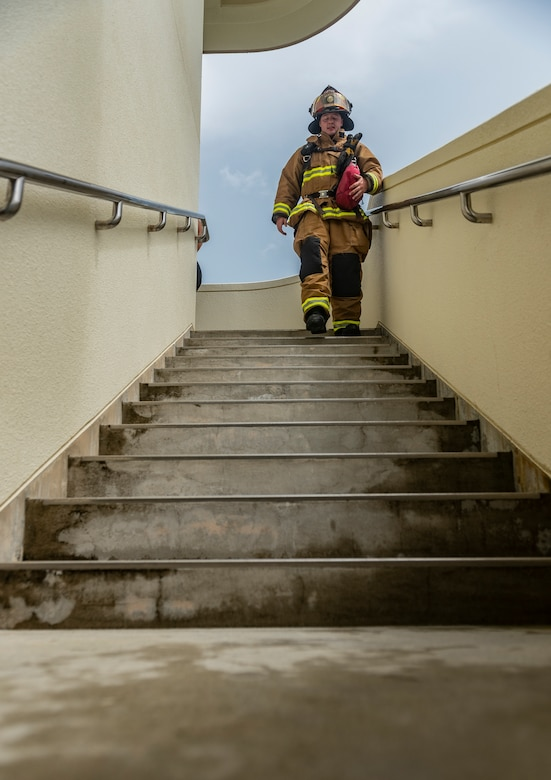 U.S. Air Force Staff Sgt. Nicholas Schafer, 18th Civil Engineer Squadron lead firefighter, walks down a flight of stairs during the Kadena Fire Emergency Services 9/11 Memorial Stair Climb Sept. 11, 2018, at Kadena Air Base, Japan. Firefighters participating in the event donned approximately 60 pounds of gear and climbed a total of 110 flights of stairs to simulate the climb firefighters made during the Sept. 11, 2001, terrorist attacks at the World Trade Center in N.Y.  (U.S. Air Force photo by Staff Sgt. Micaiah Anthony)