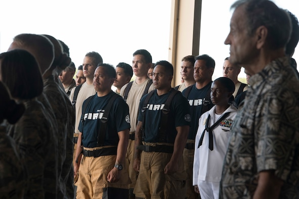 U.S. Air Force Tech. Sgt. Justin Sabio, center, a firefighter with the Air Force Reserve's 624th Regional Support Group, stands among first responders during a 9/11 Remembrance Ceremony at the Hickam Field Fire Department at Joint Base Pearl Harbor-Hickam, Hawaii, Sept. 11, 2018. Sabio works full time with the Navy Federal Fire as an advanced emergency medical technician and serves part-time as a firefighter with the 624th Civil Engineer Squadron. The ceremony honored the heroic actions of first responders who answered the nation's call that fateful day and recognized men and women who currently serve. (U.S. Air Force photo by Master Sgt. Theanne Herrmann)