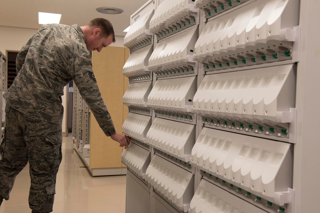 U.S. Air Force Tech. Sgt. Ryan Marr, 18th Medical Group pharmacy NCOIC, fills a prescription bottle from a pill-counting machine Sept. 10, 2018, at Kadena Air Base, Japan. Technicians use automated machines to count prescriptions involving large quantities of tablets to expedite their processes.