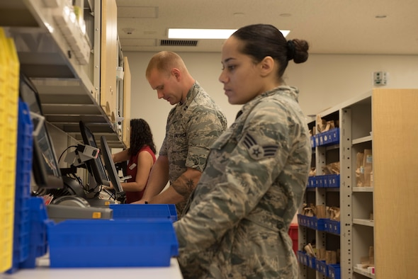 U.S. Air Force Senior Airman Cheyenne Wright, 18th Medical Group pharmacy technician, and Capt. Allen Houser, 18th MDG pharmacy operations officer-in-charge, check and fill prescriptions Sept. 10, 2018, at Kadena Air Base, Japan. Technicians ensure patients receive the appropriate number of the correct tablets as determined by their medical providers.