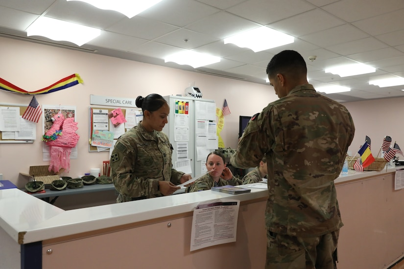 Soldiers review paperwork at a field hospital.