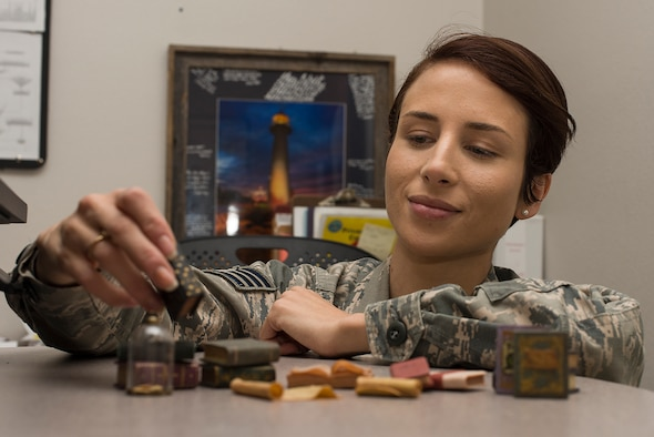 Staff Sgt. Barbara Panama, 47th Medical Group uniform business office manager, inspects on of the clay miniatures on display in her office on Sept. 12, 2018 at Laughlin Air Force Base, Texas. Panama has been crafting miniatures since she was 12, and says creating things helps her focus her energy and relieves stress. (U.S. Air Force photo by Airman 1st Class Anne McCready)