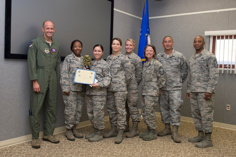 Brig. Gen. E. John Teichert, 412th Test Wing commander (far left), and Chief Master Sgt. Roosevelt Jones, 412th TW command chief (far right), join 412th Medical Support Squadron staff for a photo after Staff Sgt. Delores Otte was presented with a promotion certificate to technical sergeant Sept. 10. Otte was promoted through the Stripes for Exceptional Performance program, which recognizes and promotes outstanding Airmen. (U.S. Air Force photo by Joseph Pol Sebastian Gocong)