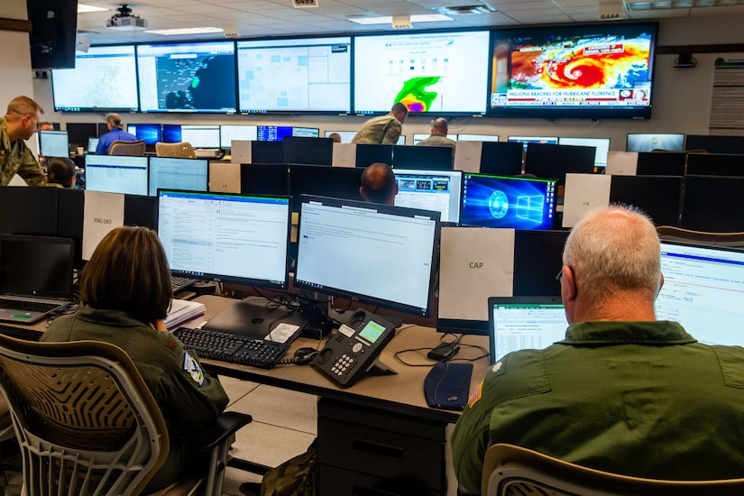Military personnel sit in front of monitors in an operations center.