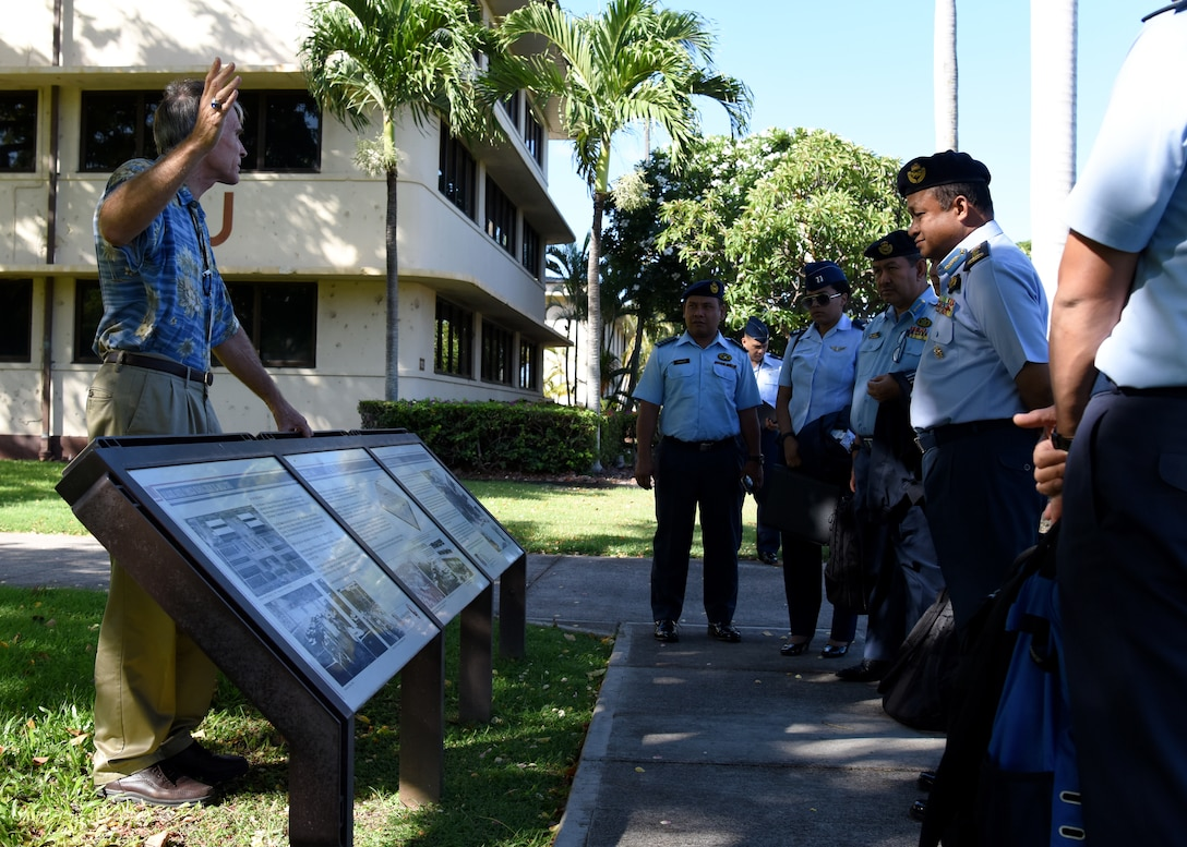 Members of the Royal Malaysian Air Force (RMAF) listen to Charles Nicholls, U.S. Pacific Air Forces (PACAF) historian, during a PACAF Headquarters and Courtyard of Heroes tour on Joint Base Pearl Harbor-Hickam, Hawaii, Sept. 5, 2018.