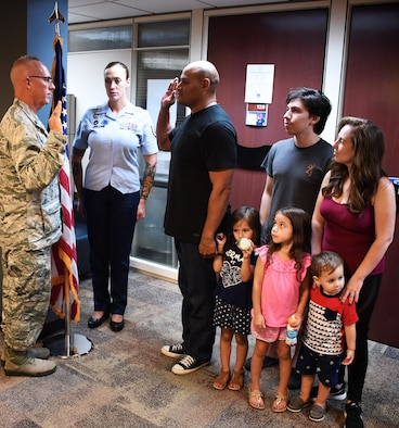 """Family showed up to witness Lt. Col. Stan Paregien perform the oath of enlistment for Bernard Collins, as his recruiting specialist, Tech Sgt. Brittany Paus looks on in background.  """"This is my WHY...Today is proof... When you Fight the Good Fight for others... The ripple of victory does follow,"""" said 932nd Airlift Wing recruiter Tech Sgt. Brittany Paus.  This veteran and his family patiently trusted the administrative process, which took about two years from when they started his application.  """"I am so grateful to welcome back Tech Sgt Collins and his family to service!  Every enlistment means a great deal, being a small vessel towards life changing chapters.  Moments like these, simply reinforce the humble honor the role of 'Recruiter' truly is,"""" Paus added.  Congratulations Tech. Sgt. Brittany Paus on her background work on behalf of Sergeant Collins and the Collins Family as he starts his next chapter as a Citizen Airman and Air Reserve Technician in the maintenance world!  (U.S. Air Force photo by Senior Master Sgt. Melissa Melichar)"""