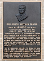 The new Reid Health Services Center bears the original bronze plaque from the 1994 dedication in honor of the late Senior Master Sgt. David B. Reid, a former first sergeant who was killed in a C-130 plane crash in 1985. The new clinic is sited on Joint Base San Antonio-Lackland, Texas, adjacent to the previous Reid Clinic located on the south edge of the new Basic Military Training Complex. (U.S. Air Force photo by Staff Sgt. Kevin Iinuma)
