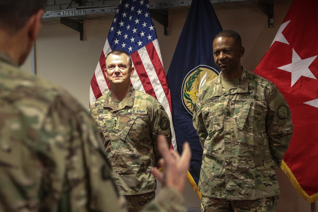 Army Lt. Gen. Paul E. Funk II, outgoing commanding general of Combined Joint Task Force Operation Inherent Resolve, left, and Army Command Sgt. Maj. Michael A. Crosby Jr., stand together while Army Gen. Joseph L. Votel, commander of U.S. Central Command, gives a speech as part of a military decorations ceremony in Baghdad.