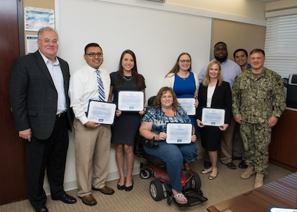 PANAMA CITY, Florida - Naval Surface Warfare Center Panama City Division (NSWC PCD) personnel, who are part of the interdisciplinary Naval Sea Systems Command (NAVSEA) People's Integrated Essential Resource (PIER) team, are recognized with a Special Act Award for their contributions to the NAVSEA Enterprise project Sept. 13, 2018. Pictured from left to right: NSWC PCD Technical Director Ed Stewart (SES), David Galindo, Katherine Mapp, Allison Roberts, Kimberly Ten Broeck, Holly Gardner, Keely Westbrook, Vatana An, and NSWC PCD Commanding Officer Capt. Aaron Peters, USN. U.S. Navy photo by Anthony Powers