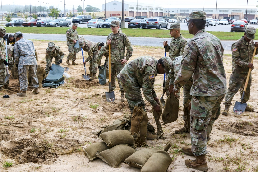 Soldiers fill sandbags.