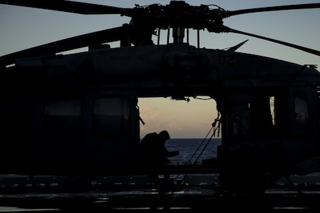 A Sailor with Helicopter Sea Combat Squadron 25 sits inside a U.S. Navy MH-60S Seahawk helicopter atop the flight deck of the amphibious assault ship USS Wasp (LHD 1) as the sun sets off the coast of Okinawa, Japan, Aug. 25, 2018.