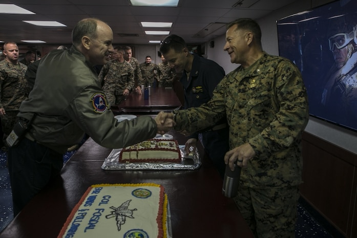 Col. Scott Fosdal, Expeditionary Operations Training Group senior evaluator, shakes hands with Marines and Sailors during a celebration honoring his retirement aboard the amphibious assault ship USS Wasp (LHD 1), off the coast of Okinawa, Japan, Sep. 3, 2018.