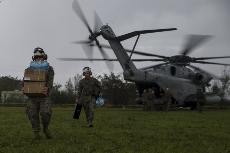 Marines with Combat Logistics Battalion 31 carry supplies from a CH-53E Super Stallion with Marine Medium Tiltrotor Squadron 262 (Rein.) during typhoon relief efforts in Rota, Northern Mariana Islands, Sept. 11, 2018.