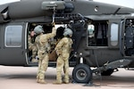 Sgt. Kelby Shifflett, center, and Sgt. Anthony McCall, right, UH-60 Black Hawk crew chiefs, assigned to Charlie Company, 1-169 General Support Aviation Battalion, Oklahoma Army National Guard, conduct pre-flight checks on the external rescue hoist prior to leaving to support relief efforts for Hurricane Florence Sept. 13, 2018. Seven Soldiers from the aviation unit trained in Helicopter Search and Rescue operations will conduct swift water rescues using dynamic and static hoists to rescue stranded citizens after the hurricane subsides.