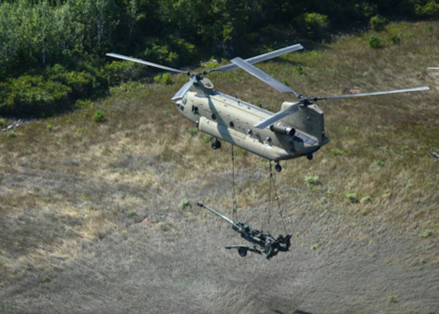 A CH-47 Chinook helicopter from 2nd General Support Aviation Battalion, 135th Aviation Regiment, Colorado Army National Guard, airlifts an M777 105mm Howitzer from Camp Grayling, Michigan, to an area in the vicinity of the Combat Readiness Training Center in Alpena, Michigan, Aug. 10, 2018.
