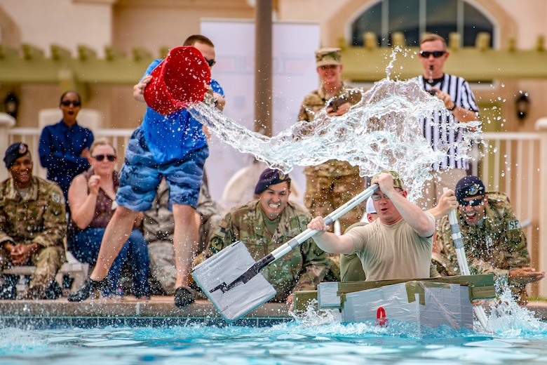 "Staff Sgt. Chad Bohr and Tech. Sgt. Tyler Dalton, 377th Weapons System Security Squadron, are splashed by spectators during the Battle of the Battleships, at Kirtland Air Force Base, N.M., Aug. 30, 2018. Bohr and Dalton's ship, ""Ops Boat,"" placed second overall. (U.S. Air Force photo by Staff Sgt. J.D. Strong II)"