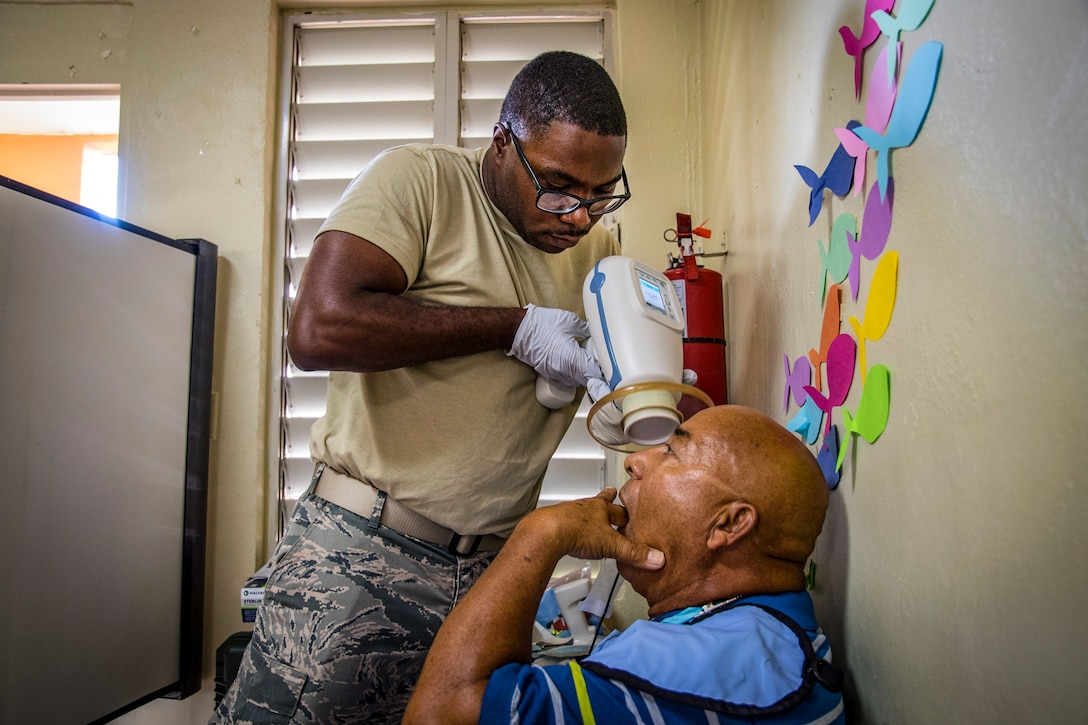 Staff Sgt. Dennis King, 105th Medical Group dental assistant, executes dental X-ray procedures on a resident of Catano, Puerto Rico, during Innovative Readiness Training Ola de Esperanza Sanadora, Aug. 31, 2018. The IRT provides medical, dental and optometry care to assist local municipal authorities in addressing underserved community health and civic needs while performing joint military humanitarian operations. (U.S. Air National Guard photo by Staff Sgt. Bethany Rizor)