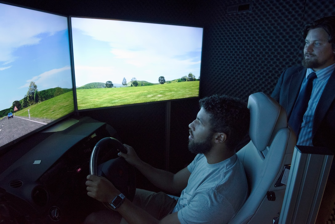 """NASCAR driver Darrell """"Bubba"""" Wallace Jr., test drives a simulated vehicle inside the biomedical research lab at the U.S. Air Force School of Aerospace Medicine, Wright-Patterson Air Force Base, Ohio, Sept. 7, 2018. The research is used for assessing aircrew fatigue and system performance. (U.S. Air Force photo by Michelle Gigante)"""