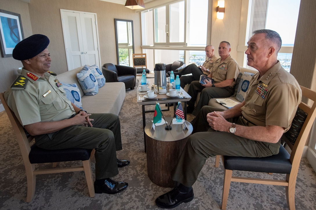 Two defense leaders sit across from each other during a meeting.