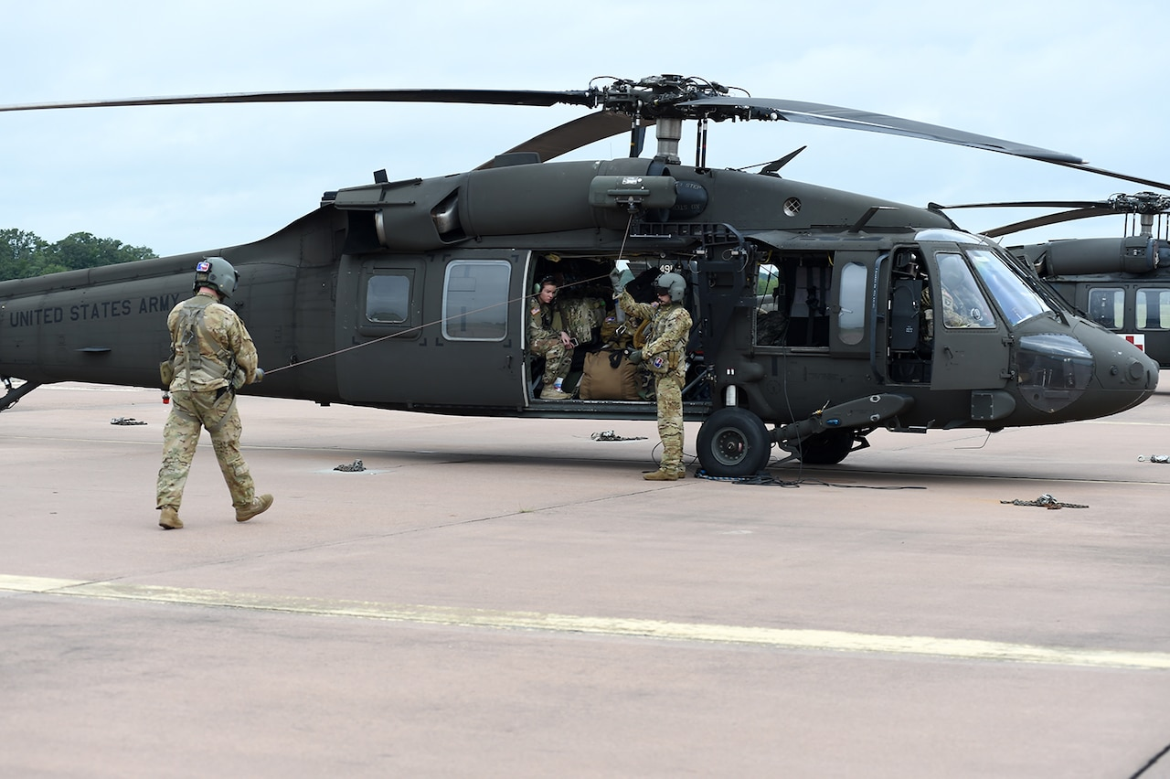 Army Sgt. Kelby Shifflett, left, and Sgt. Anthony McCall, right, UH-60 Black Hawk helicopter crew chiefs assigned to Charlie Company, 1st General Support Aviation Battalion, 169th Aviation Regiment, Oklahoma Army National Guard, conduct preflight checks.