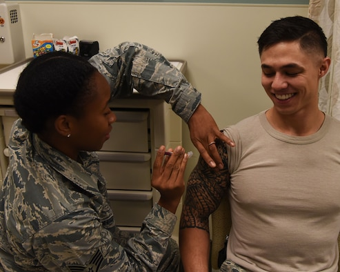 Staff Sgt. Gisele Adanlete-Engram, 56th Medical Group aerospace medical technician, administers a shot to Staff Sgt. Daniel Durbin, 56th MDG Immunizations backup technician, Sept. 13, 2018 at Luke Air Force Base, Ariz.