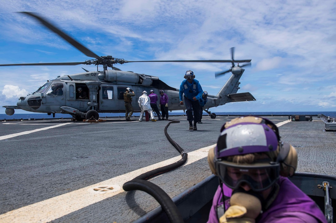 Sailors refuel a helicopter aboard a ship.