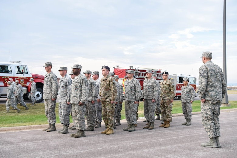 Members of the 28th Civil Engineer Squadron fire department, emergency medical services and the 28th Security Forces Squadron form up at the 9/11 memorial ceremony outside of the 28th Bomb Wing headquarters at Ellsworth Air Force Base, S.D., Sept. 11, 2018. As a result of the 9/11 terrorist attack, 412 first responders died and countless others were injured while trying to save the lives of others. (U.S. Air Force photo by Airman Christina Bennett