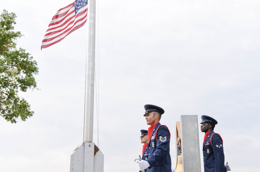 Members of the 28th Civil Engineer Squadron fire department stand for a moment of silence outside of the 28th Bomb Wing headquarters at Ellsworth Air Force Base, S.D., Sept. 11, 2018. The flag is flown at half-staff in honor of the people that lost their lives as a result of the 9/11 terrorist attack. (U.S. Air Force photo by Airman Christina Bennett)