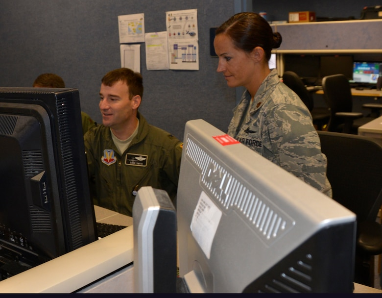 Col. Dave Smith, 601st Air Operations Center Air Mobility Division chief, reviews mobility and airlift documents with Maj. Sarah Boone, Director, Mobility Forces team member. From providing specialized job personnel and equipment to assigning staging areas for supplies, Air Forces Northern, the air component of U.S. Northern Command, continues to assist that command's support of the Federal Emergency Management Agency's Hurricane Florence relief efforts. (Air Force photo by Mary McHale)