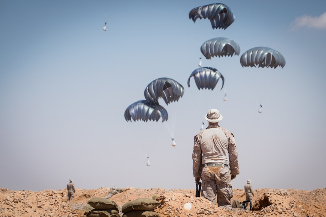 SOUTHWEST ASIA – A U.S. Marines with 3rd Battalion, 7th Marine Regiment, attached to Special Purpose Marine Air-Ground Task Force, Crisis Response-Central Command (SPMAGTF-CR-CC), observes as a supplies are dropped in the De-confliction Zone (DCZ) near At-Tanf Garrison, Syria, Sept. 7, 2018. SPMAGTF-CR-CC Marines supported Special Operations Joint Task Force – Operation Inherent Resolve by conducting a company-sized drill demonstrating the ability to quickly fortify the DCZ as well as conducting multiple live-fire ranges.  (U.S. Marine Corps photo by Cpl. Carlos Lopez)