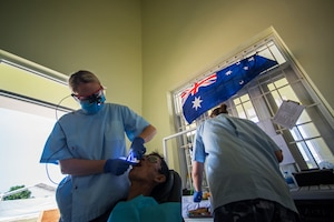 (Left) Royal Australian Air Force Flight (RAAF) Lieutenant Jess Raine,  RAAF dentist works with RAAF Cpl. Hannah Fortington, a senior dental assistant, to perform a tooth extraction on Luong Van Kiem during Pacific Angel (PAC ANGEL) 18-2 at the Cultural House of Tam Giang commune in Nui Thanh, Quang Nam province, Vietnam, Sept. 12, 2018.